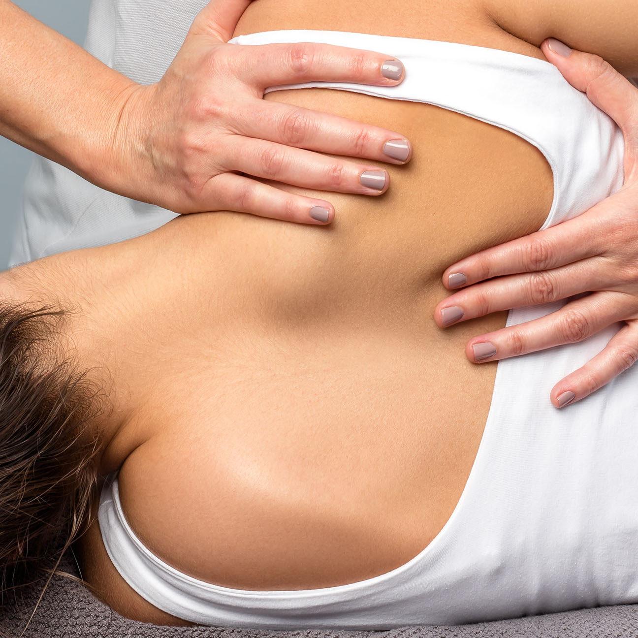 Detail of female therapist manipulating shoulder blade on patient.